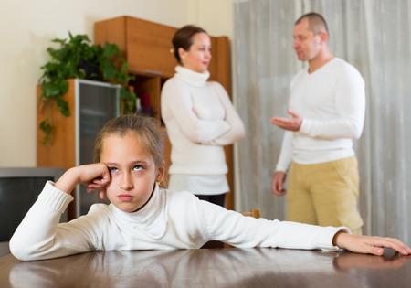 fracas: Parents and daughter quarrel at the home. Focus on girl Stock Photo