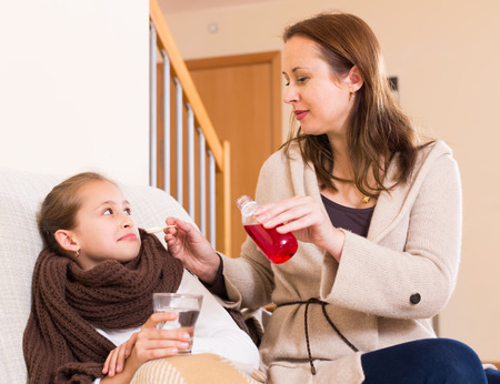 seven persons: Mother giving medicinal sirup to sick little daughter at home Stock Photo