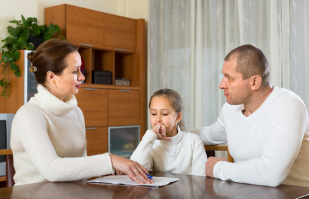 avidity: Sad family with daughter solving financial problems at the table at home