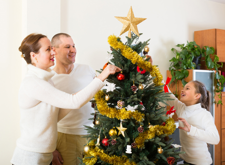 decorating christmas tree: Smiling family with daughter decorating Christmas tree in the living room at home. Focus on woman Stock Photo