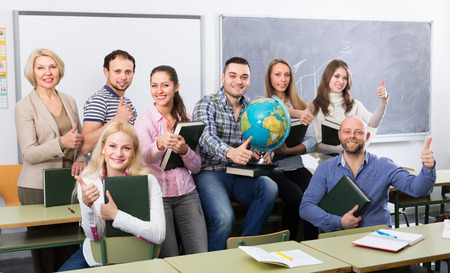 cohesive: Female professor and cheerful students posing in classroom at extension courses