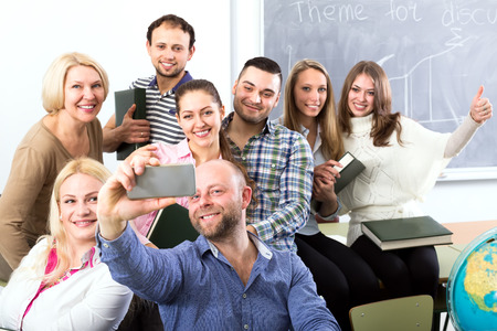 cohesive: Teacher making a selfie of him with his students in a classroom Stock Photo