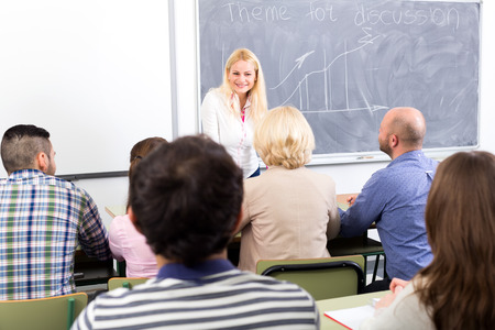 mixed age: Happy trainer at courses for personal growth speaking in front of her mixed age students Stock Photo