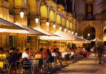personas en la calle: restaurantes en plaza Real en la noche de verano. Barcelona, ??Catalu�a Editorial