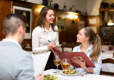 riendo: Camarera Hospitalario teniendo una orden de una pareja en un restaurante rural Foto de archivo