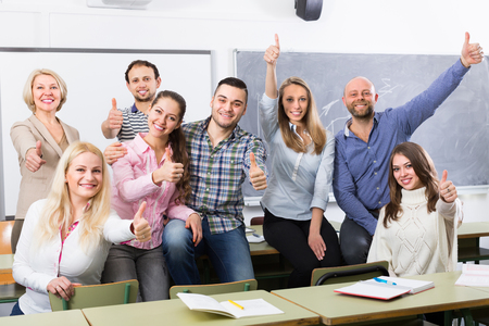 informal clothing: Smiling professor and cheerful students posing in classroom at extension courses Stock Photo