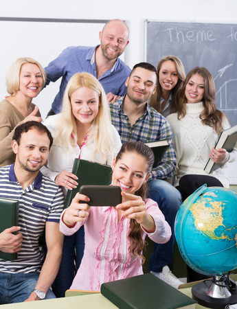 informal clothing: happy students of different age doing group selfie on smartphone