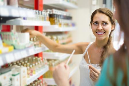Smiling american girl Kauf Parfüm in der Shopping-Mall Standard-Bild