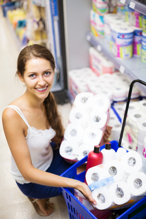 woman toilet: Smiling girl choose toilet paper in the shop Stock Photo