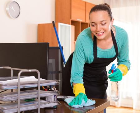 household tasks: Smiling young cleaning woman wiping the table at office room