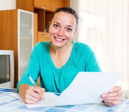 filling out: Beautiful woman filling out tax forms while sitting at her desk