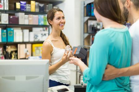 store clerk: Smiling female store clerk serving purchaser at cash desk