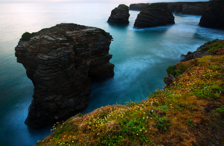 influx: Cliffs at  Atlantic Ocean coast in  twilight.  As Catedrais beach during high tide. f Spain