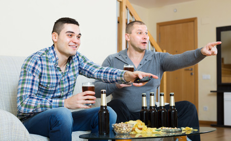 Two excited men drinking beer and watching football game indoor