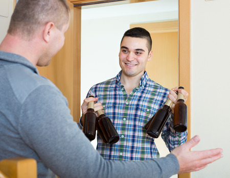 adult male: Two happy smiling adult male friends gathering to drink beer at home