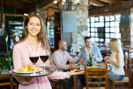 waitress: Portrait of a smiling female waiter with a tray in his hand at the restaurant