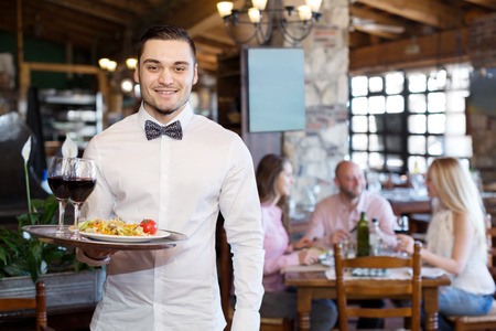 camarero: Retrato de un camarero masculino feliz con una bandeja en la mano en el restaurante Foto de archivo