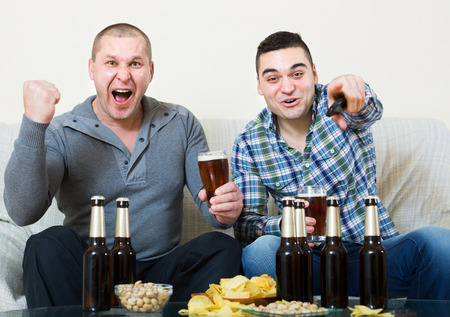 fandom: Two excited male friends drinking beer and watching football game at home Focus on one Stock Photo