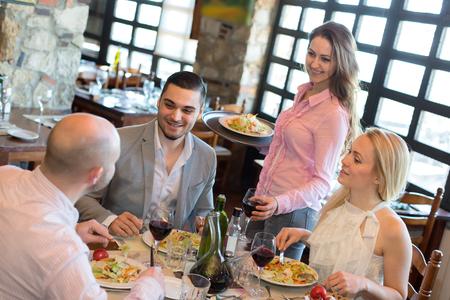 Una empresa de personas para cenar en un restaurante mientras sonriente camarera les está sirviendo Foto de archivo