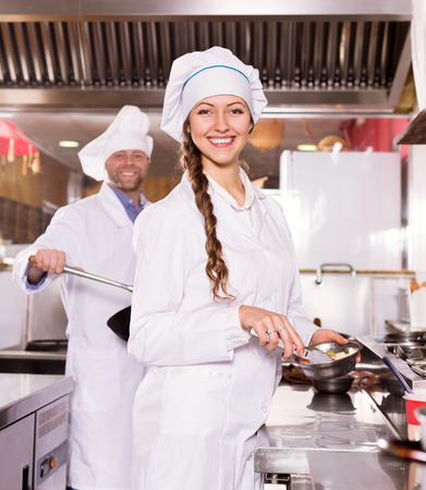 female clothing: portrait young woman cook cooking at professional kitchen in the take-away  restaurant