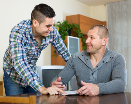 life insurance: Young male agent consulting client about terms of life insurance at home Stock Photo