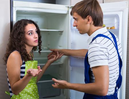 refrigerator kitchen: Tired handyman cannot repair refrigerator in domestic kitchen
