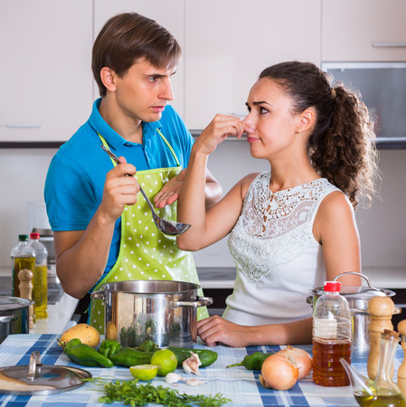 foul: Surprised adults feeling foul smell of food from casserole in  domestic interior Stock Photo