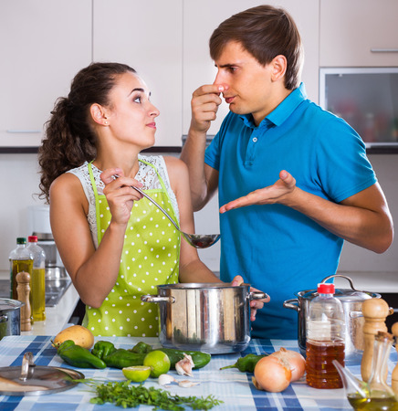 stinking: Portrait of young couple with stinking veggies food in domestic kitchen