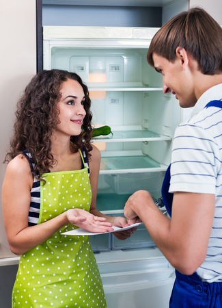 fridge: Happy housewife grateful to professional mechanic for help with fridge Stock Photo
