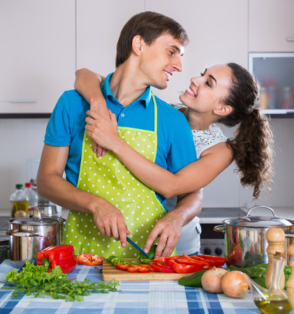 russian man: smiling russian man and woman standing near table with vegetables