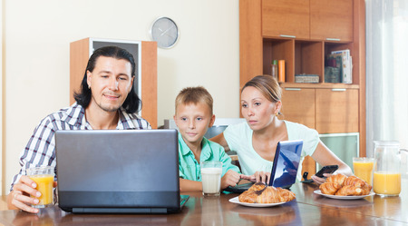 breackfast: Happy adult couple with teenager having breackfast in the morning with the electronic device in the home interior