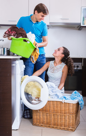 spouses: happy spouses doing regular laundry and smiling at home Stock Photo