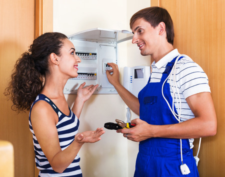 electric meter: Young woman and repairman near electric meter in domestic interior Stock Photo