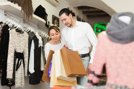 gladful: Couple with shopping bags at clothing shop together Stock Photo
