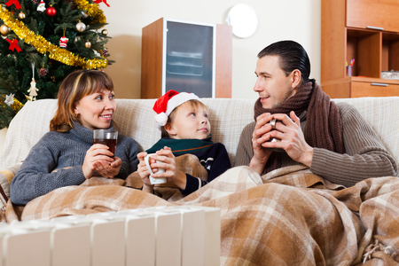 heat register: parents and teenage son warming near warm heater in Christmas time