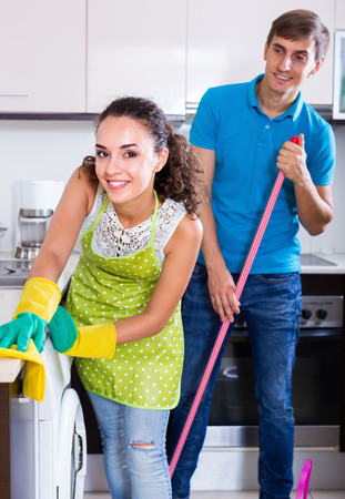 spouses: Young spouses doing  regular cleanup and polishing in domestic kitchen
