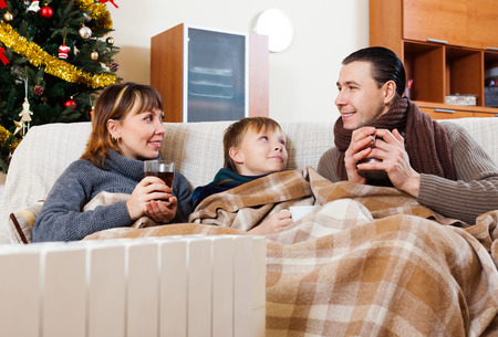 Happy family of three with cups of tea warming near warm radiator in Christmas time at home