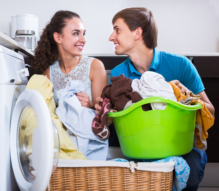 spouses: Young spouses doing  laundry and smiling at home