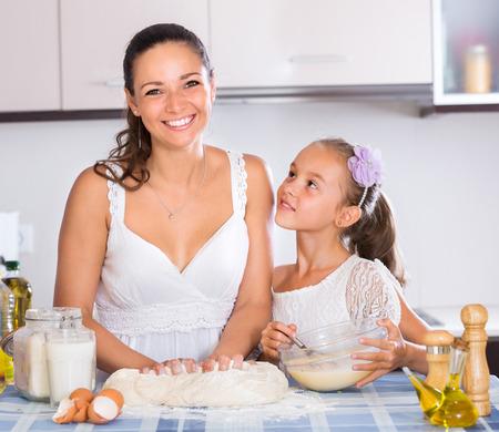 stiff: Cheerful female and girl kneading stiff dough in kitchen Stock Photo