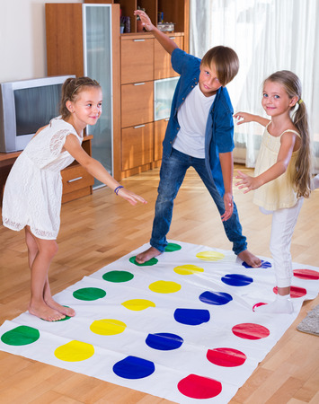 romp: Group of happy children playing at twister in living room Stock Photo