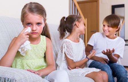 unfaithfulness: Envy child sitting aside of two children at home