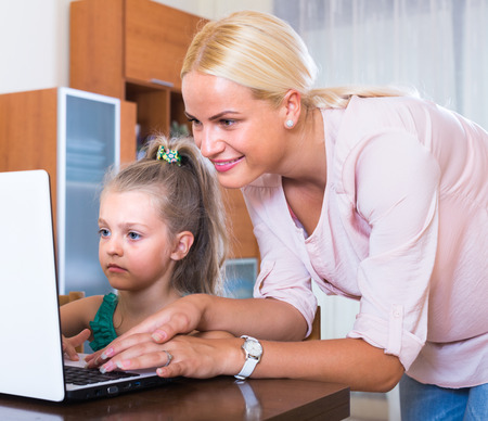 relatives: Smiling woman watching her little daughter chatting with relatives online
