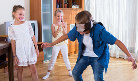 bluff: Blindfolded boy catching other little players in Kagome at home. Selective focus Stock Photo