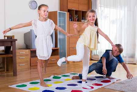 twister: Two cute little girls and teenage boy playing twister at home Stock Photo