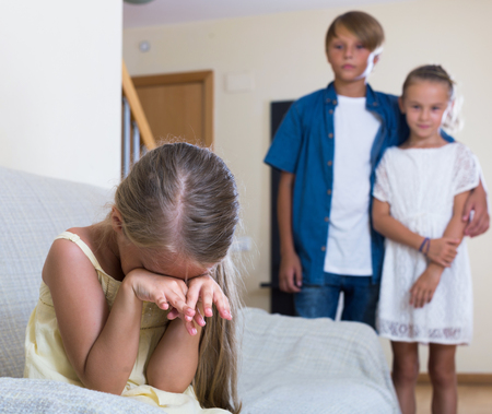 amorousness: First amorousness: sad european girl and couple of kids apart indoors