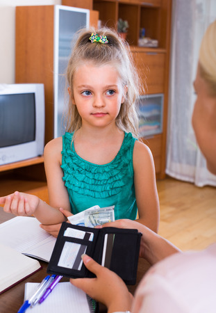 Allowance of pocket money: cute little girl and mother with purse at home