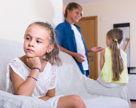 amorousness: First amorousness: unhappy american girl and couple of kids apart indoors Stock Photo
