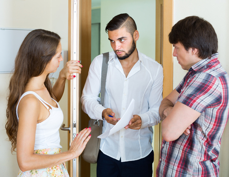 repayment: Bank agent came home to the young couple clamouring credit repayment Stock Photo