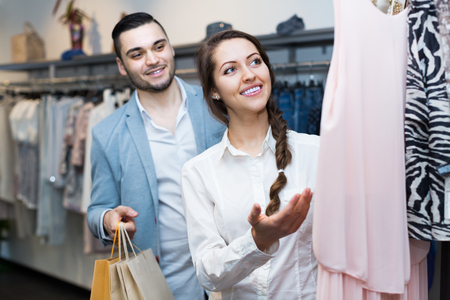 russian man: Male customer consulting with smiling female shop assistant. Focus on girl Stock Photo
