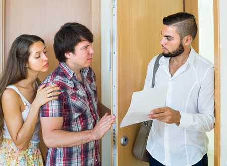 repayment: Agent clamouring credit repayment from young couple at the doorway